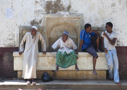 Group of people sitting on a fountain, Lamu county, Lamu, Kenya