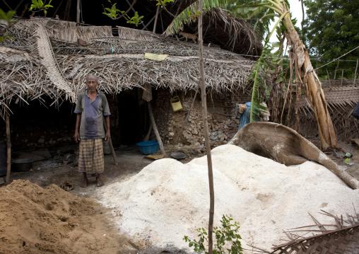 Man standing with amount of powdered shell, Lamu kenya