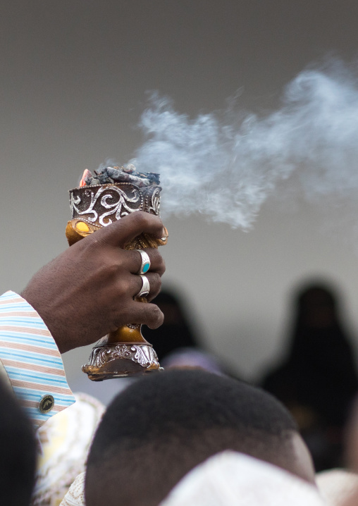 Sunni muslim man spreading insence with a censer during the maulidi festivities in the street, Lamu county, Lamu town, Kenya