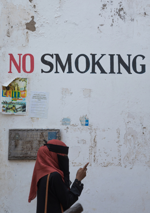 Muslim woman in burqa under a no smoking sign on a wall using her mobile phone, Lamu county, Lamu town, Kenya