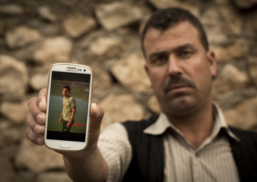 Yezedi Refugee From Sinjar Showing The Picture Of His Dead Relative Killed By Daesh On His Mobile Phone, Lalesh Temple, Kurdistan, Iraq