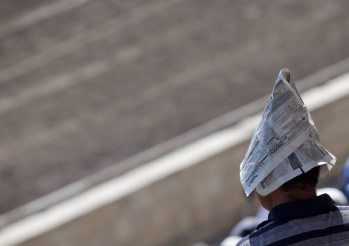 Man Using A Newspaper As An Improvised Hat To Protect From The Sun During The Horse Game On National Day, Bishkek, Kyrgyzstan