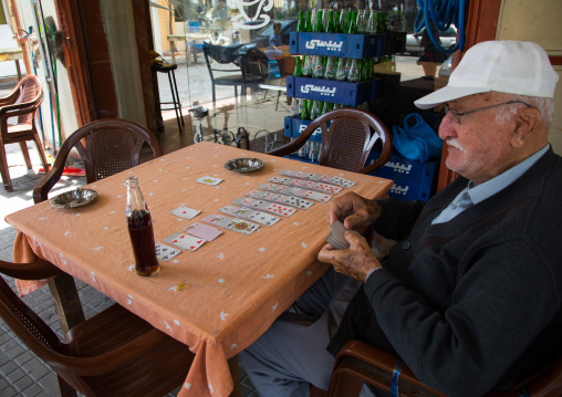 Old man playing cards alone at cafe table, North Governorate, Tripoli, Lebanon