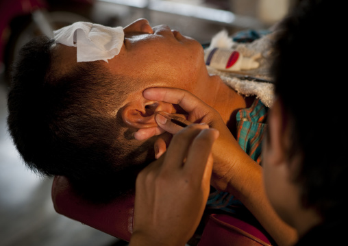 Hairdresser taking care of the ears, Pakse, Laos