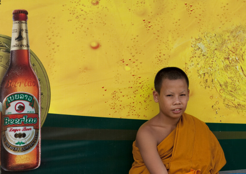 Monk in front of a beer advertising at a bus stop, Pakse, Laos