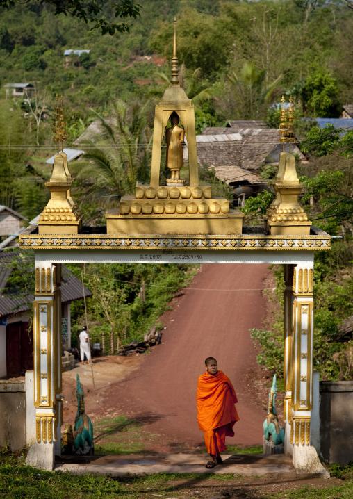 Monk at the entrance of phra saek kham temple, Muang la, Laos
