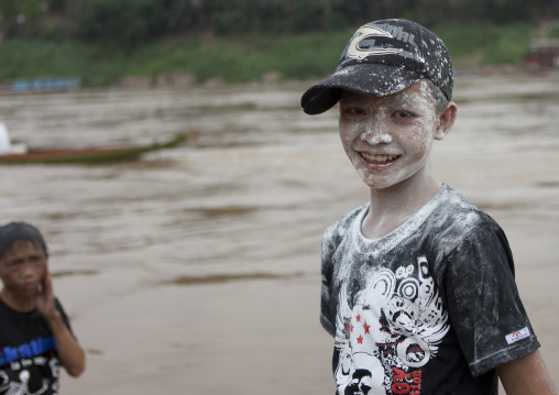 Boy with flour on the face during pii mai lao new year celebration, Luang prabang, Laos
