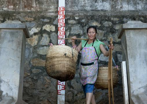 Woman carrying baskets on the banks of the mekong, Luang prabang, Laos