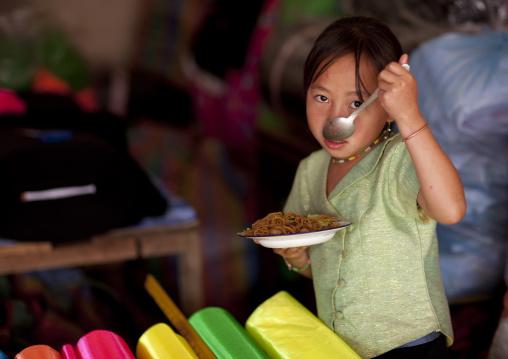 Girl eating in a shop, Phonsavan, Laos