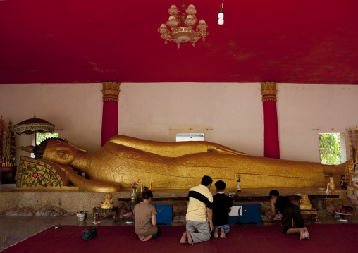 People praying in front of lying buddha statue, Pha bat monastery, Pakse, Laos
