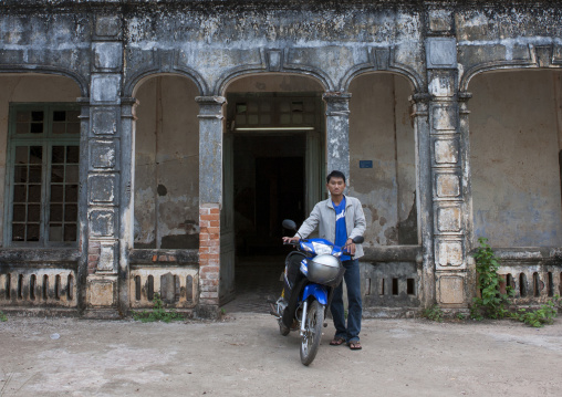 Man on his motorbike in front of an old french colonial house, Thakhek, Laos