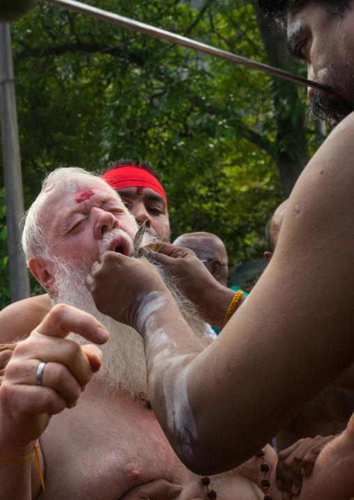 Carl, An Australian Hindu Devotee Cheek Is Pierced By A Priest At Thaipusam Hindu Festival At Batu Cave, Southeast Asia, Kuala Lumpur, Malaysia