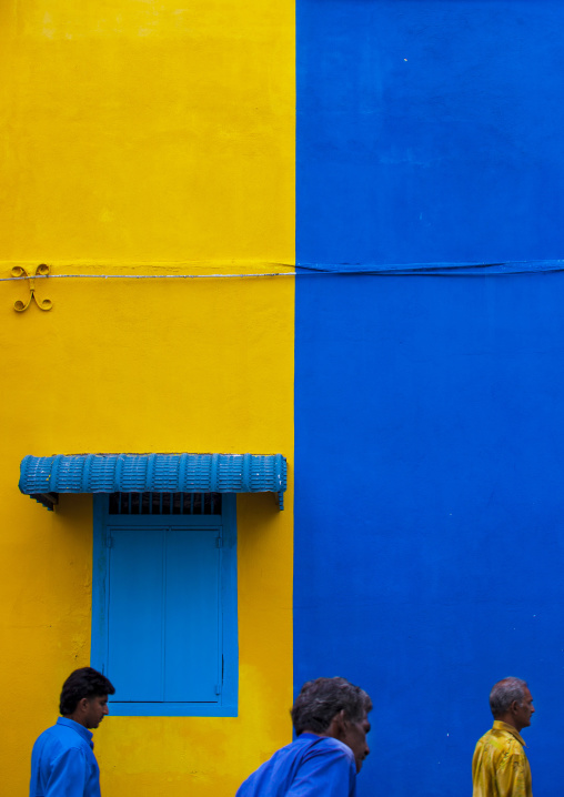 Men Passing In Front Of Yellow And Blue Wall In The Street, George Town, Penang, Malaysia
