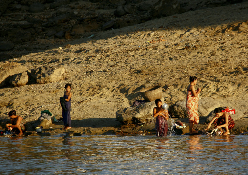 Women taking bath on irrawaddy river banks, Myanmar