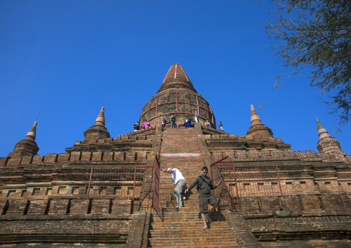 Tourist climbing on an old temple, Bagan, Myanmar