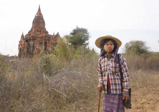 Sheperd woman in front of an old temple, Bagan, Myanmar