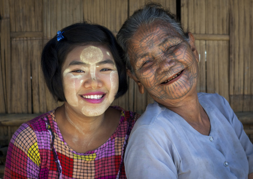 Tribal chin woman with spiderweb tattoo on her face with her little daughter, Mrauk u, Myanmar