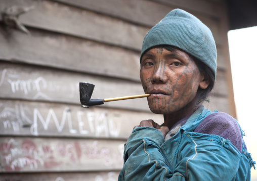 Tribal chin woman from muun tribe with tattoo on the face smoking, Mindat, Myanmar