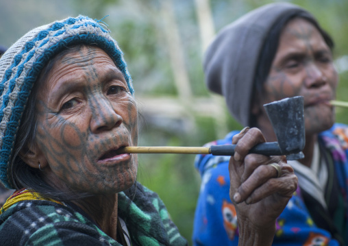 Tribal chin women from muun tribe with tattoos on the face smoking, Mindat, Myanmar