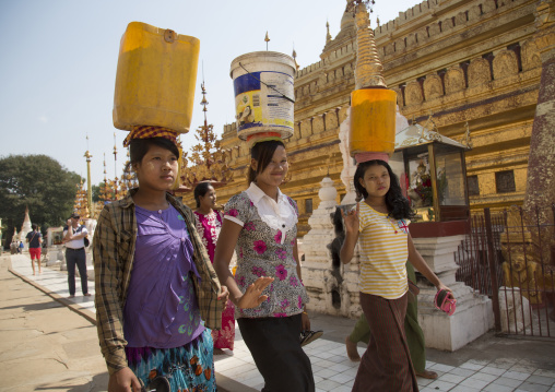 Workers passing in front of shwe zigon paya golden temple, Bagab, Myanmar