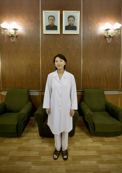 North Korean doctor at the maternity posing below the official portraits of the Dear Leaders, Pyongan Province, Pyongyang, North Korea