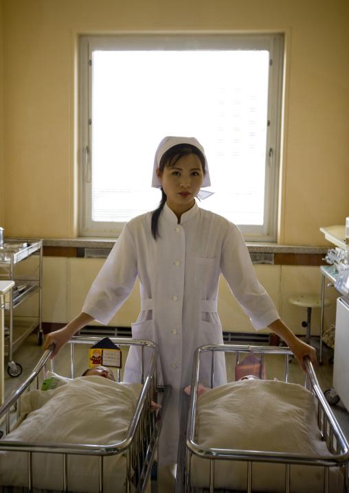North Korean nurse with newborn babies in a maternity, Pyongan Province, Pyongyang, North Korea