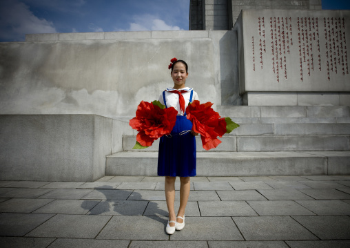 North Korean pioneer girl with flowers ready for the parade in front of the Juche tower, Pyongan Province, Pyongyang, North Korea