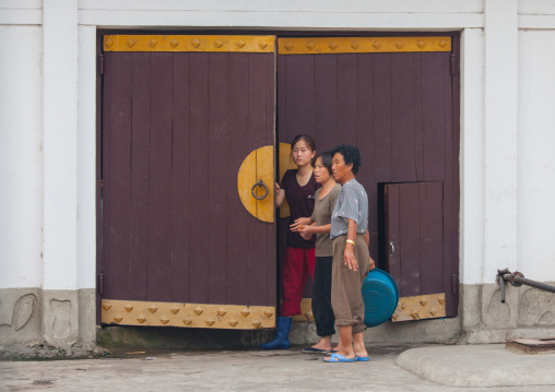 North Korean women in front of a traditional wooden door, North Hwanghae Province, Sariwon, North Korea