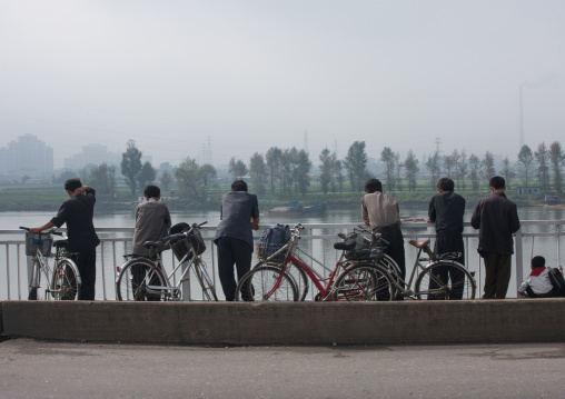 North Korean men looking over Taedong river, Pyongan Province, Pyongyang, North Korea