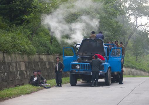 North Korean men repairing a smoking vapor truck on a highway, North Hwanghae Province, Chilbo Sea, North Korea