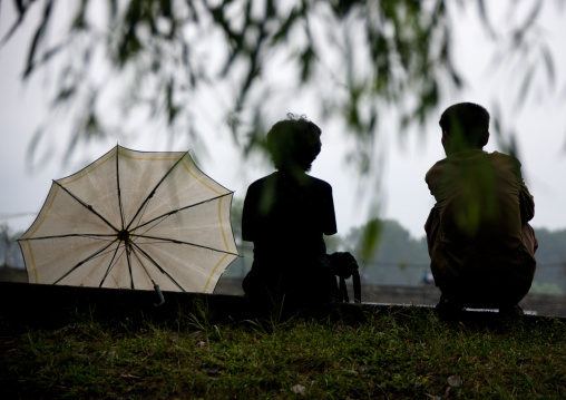 Silhouettes of a North Korean couple sit together, South Hamgyong Province, Hamhung, North Korea