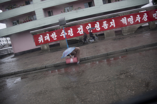 North Korean woman bending over in the street, South Hamgyong Province, Hamhung, North Korea