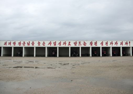 Storage for farm vehicles with a slogan on the top, South Hamgyong Province, Hamhung, North Korea