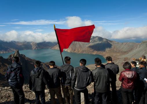 Group of students with red flag in front of lake at mount Paektu, Ryanggang Province, Mount Paektu, North Korea