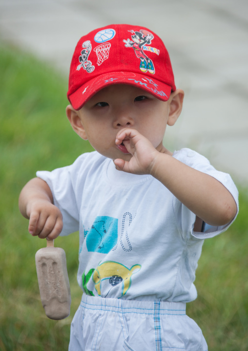 Portrait of a North Korean toddler with a Mickey mouse cap eating an ice cream, Pyongan Province, Pyongyang, North Korea