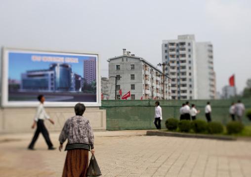 North Korean people walking in front of propaganda billboards, Pyongan Province, Pyongyang, North Korea