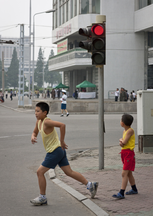 North Korean boys crossing a street under a traffic light, Pyongan Province, Pyongyang, North Korea