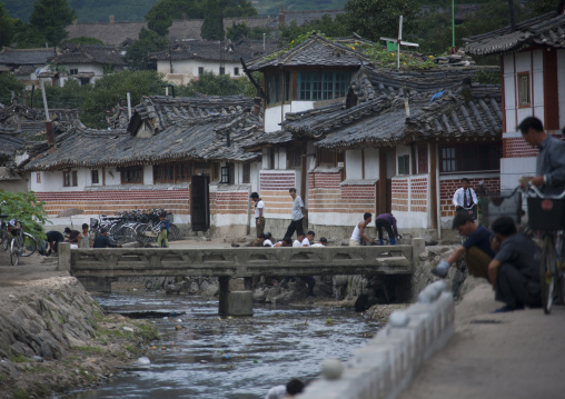 North Korean people crossing bridge over a little river in the old town, North Hwanghae Province, Kaesong, North Korea