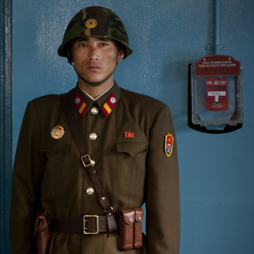 North Korean soldier wearing an helmet standing in front of the United Nations conference rooms on the demarcation line in the Demilitarized Zone, North Hwanghae Province, Panmunjom, North Ko