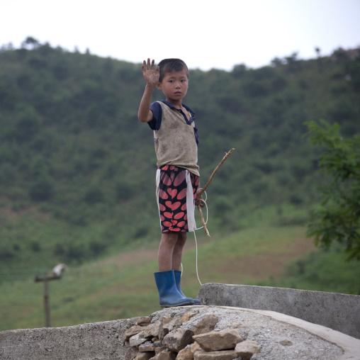 Grubby North Korean boy waving hand, North Hwanghae Province, Kaesong, North Korea