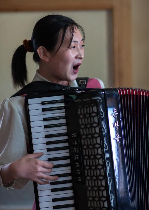 North Korean waitress in a restaurant singing and playing accordion, Pyongan Province, Pyongyang, North Korea