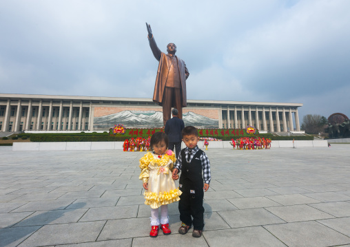 Two North Korean children in front of Kim il Sung statue in the Grand monument on Mansu hill, Pyongan Province, Pyongyang, North Korea