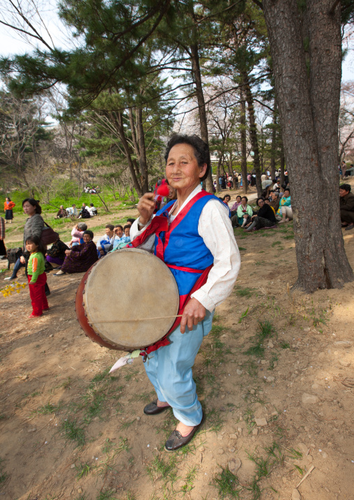 North Korean woman playing drum in a park for the day of the sun which is the birth anniversary of Kim Il-sung, Pyongan Province, Pyongyang, North Korea