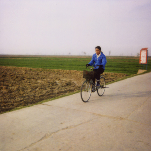Polaroid of a North Korean girl riding a bicycle in the countryside, North Hwanghae Province, Kaesong, North Korea