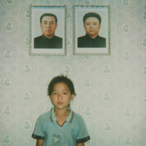 North Korean girl posing below the portraits of the Dear Leaders inside her home, South Pyongan Province, Chonsam Cooperative Farm, North Korea