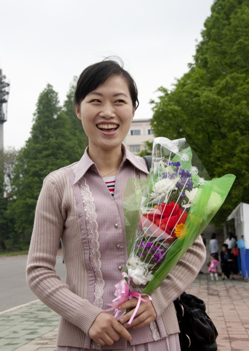 Smiling North Korean woman with a bunch of flowers in Mansudae Grand monument, Pyongan Province, Pyongyang, North Korea