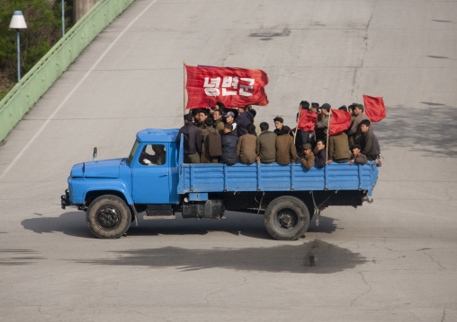 North Korean workers on a truck with red flags going to work, North Pyongan Province, Myohyang-san, North Korea