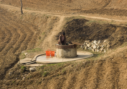 North Korean woman collecting water in a well in the countryside, South Pyongan Province, Nampo, North Korea
