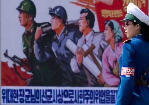 North Korean female traffic officer in front of a propaganda billboard in the street, Pyongan Province, Pyongyang, North Korea