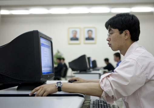 North Korean man using a computer under the Dear Leaders pictures in the Grand people's study house, Pyongan Province, Pyongyang, North Korea